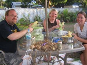 Mike, Amanda and Sara shuck corn.  Amanda's homegrown onions are in the foreground.