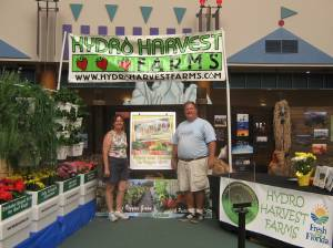 Terrie & John Lawson stand in front of their display at the Epcot Florida Farmers Market